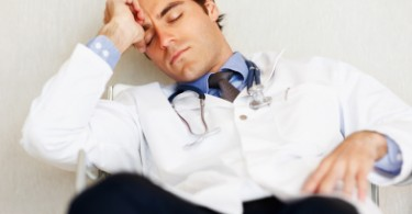 Portrait of a young male doctor sleeping on chair at hospital